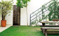 As cruzetas aparecem em toda a área externa, com as espécies pleomele-reflexa (à eq.), limão-siciliano (à dir. do chuveiro) e jasmim-da--itália (na escada). Sobre a mesa, jarra e bandeja encontradas na Utilplast e arranjo de cactos plantados em mix de sei (Foto: Casa e Jardim)