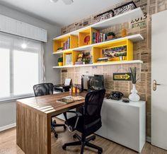 Home office para dois em 9 m² - despojado com   jornal cobrindo a parede e prateleiras amarelas, o ambiente alem de funcional fica muito alegre.
