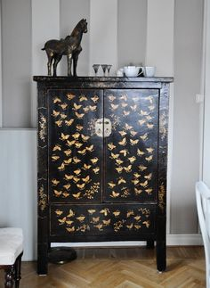 Sort of a similar feel to my rad 1920's dresser - black lacquer, gold leaf but with the added awesome of ornate legs and green glass drawer pulls.