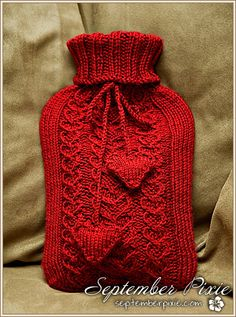 red knitted hot water bottle cover with hearts