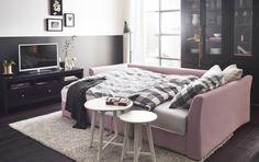 リビングルームにライトピンクのコーナーソファベッドにグレー/ホワイトのベッドリネンとネストテーブルをリビングルームに置いている。ブラックブラウンのTV台とガラス扉のキャビネットをそばに。