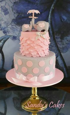 This pink and gray elephant baby shower cake has great detailing, like satin ribbon, polka dots, and ruffles, topped with a sweet mother and baby elephant! This cake will be sure to grab everyone's attention at your party! Tortas Baby Shower Niña, Gateau Baby Shower, Elephant Baby Shower Cake, Elephant Cakes, Elephant Theme, Pink Elephant, Beautiful Cakes, Amazing Cakes, Bolo Laura