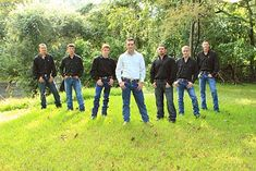Sand Dollar groomsmen in blue jeans and boots with black shirts. Cowboy wedding.