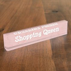"""A fun desk sign makes an ideal novelty gift for a family member, co worker or boss, in a pink wood grain effect and white writing. Feel free to change the words, """"Shopping Queen"""" to suit your needs."""