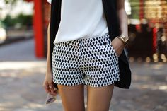 tailored graphic shorts paired with a blouse and long vest