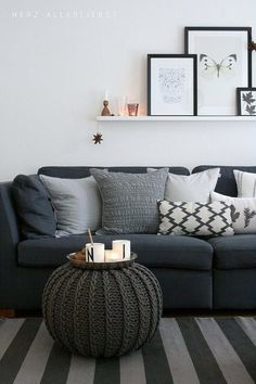 Dark gray sofa with light gray walls.  I would add pops of color with pillows on the couch.