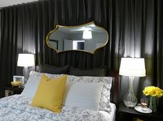 A DIY bedroom with curtains and a mirror.  Love it.
