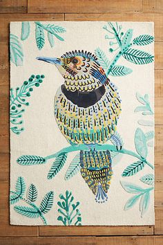 The Plumita Rug by Anthropologie focuses on a bird comprised of cool tones with warm accents.
