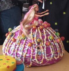 Piepschuim bal ( halve gekocht ) bekleed met roze cadeau papier en bovenin een ovaal gat er in gesneden en de barbie er in gestoken. Verder lolly's door geprikt en er een snoep ketting aangehangen.