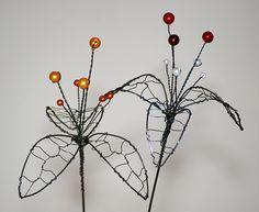 Lilie. Květina je vyrobena z černého žíhaného drátu, doplněna perličkami různých barev. Délka 39-40cm, průměr květu 11-12cm. Prosím, zadejte si v jaké barvě chcete květinu vyrobit.