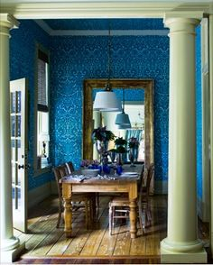 Gorgeous blue dining room with a mirror at the end of the dining table for a never-ending display!