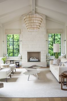 The living room of a newly-built house by designer Annette English and architect William Hefner speaks volumes, with Annette English's signature creamy and dreamy palette. A custom Ironies Jaeger chandelier and Ron Arad coffee table are the center of attention.