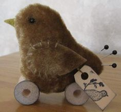 """Brown Bird made from vintage upholstery velvet. Vintage wooden spool """"wheels"""". Glass bead eyes, stick pin tail feathers. Hang tag has a bird stamped on it and is signed by me. It all measures 3"""" high."""