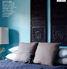 love the dark intricately carved wood against the teal/blue wall