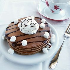 A recipe for hot cocoa pancakes made from scratch and topped with chocolate syrup and whipped cream.