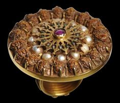 Michael Backman Ltd - Temple Gold Ring Set with Rubies, Emeralds, Pearls & Rudraksha Seeds South India 18th-19th century diameter of bezel: 4.5cm, inside diameter or hoop: 1.9cm, weight: 57g This spectacular gold ring set with twelve large freshwater pearls, 19 rudraksha seeds a central ruby and sixteen tiny emerald beads, was commissioned as temple jewellery to adorn the hand of a statue of a deity during a South Indian temple festival. The large, heavy bezel, is in the form of a marigold…