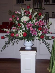 Altar Arrangement of Stargazer lilies, Medium Pink Roses, Red Roses,  White Larkspur, and Greenery assortment, contained in a White Urn