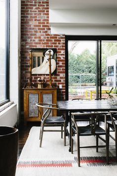 rustic dining room with wishbone chairs, exposed brick walls, and a figurative painting // dining rooms