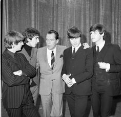 The Beatles chat with Ed Sullivan during their first appearance on his show on Feb. 9, 1964.