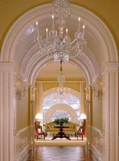 One of my favorites  Lovely white and yellow hallway with detailed arches and chandelier. Looking thru to the spectacular double round window
