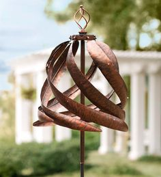 Over six feet tall, this Solar Copper-Colored Metal Wind Spinner is equipped with solar-powered LED lights on its swirling rotors that soak up the sun's rays by day to lend a white LED glow at night.