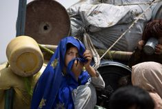 A Pakistani tribal girl sits next to her belongings on a truck after arriving to Bannu, Pakistan, Wednesday, June 18, 2014. Thousands of villagers fled as Pakistani army relax a curfew in troubled North Waziristan. Pakistani jets pounded targets in the country's northwest in major offensives designed to root out safe havens in the volatile region.