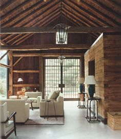 barn converted into a pool house with exposed beams, cement floors, steel and glass sliding doors