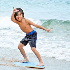 Skimboarding local boy on the beach in Makena. This photograph is the winner of Maui Family Magazine photo contest.