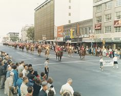 """The Dawson County Plum Creek Riders participate in Nebraska's Bicentennial Parade on """"O"""" Street in Lincoln, September 2, 1967. Clark's Clothes for Men, Household Finance, Anderson Photo Studio, Spoofer Shop, Ten-28 Fabrics and Norman's Furniture are all visible. 