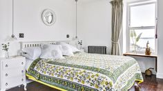 A bright floral bedspread adds pattern to a white bedroom