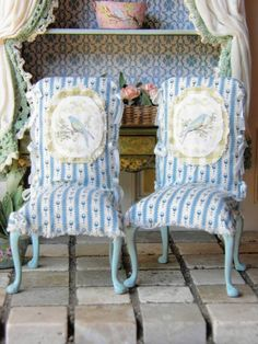 Casual Slip Cover Chairs Blue Country fabric slip covered chairs. Legs painted in robins egg blue, slightly distressed. Hand painted blue bird medallion, and tiny blue silk bows.