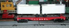 Lionel postwar # 6431 Piggyback set included a red Midgetoy tractor and a flatcar with two white trailers.