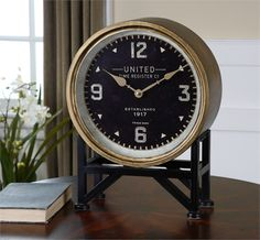 Clock Face Features A Metal Frame With A Brass Finish And Aged Black Stand…