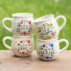 "Happy Mugs - With a handcrafted feel and generous 16-ounce size, this ""happy"" ceramic mug features ""cup of"" saying and a heart printed on the inside bottom. Perfect for gifting. Dishwasher and microwave safe."