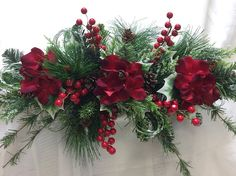Cute small winter swag made on an artificial pine base. Filled with frosted greenery, holly, red stem berries, pinecones and 3 red hydrangeas. Can be hung horizontal (recommended) or vertical. (Swag is hard to photograph therefore most photographs are taken hung vertical).