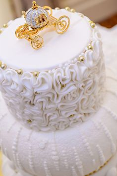 Classic white wedding cake with Cinderella's golden carriage cake topper