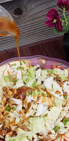 Chinese Cabbage Salad - 2-2 1/2 pounds nappa cabbage     5 green onions  3 packages ramen noodles  1/2 C butter  1/4 C sliced almonds  1/4 C sesame seeds  Dressing:  3/4 C peanut oil (or 3 T peanut butter + canola oil to equal 3/4 C)  1/2 C sugar  1/4 C rice vinegar  2 T soy sauce