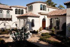 white brick exterior, mediterranean style, terracotta roof, gravel pathway, landscaping