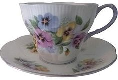 """Bone china teacup and matching saucer with a pansies pattern by Royal Albert of England, circa 1960. Marked on underside. Dimensions: teacup, 4.75""""Dia x 3""""H; saucer: 5.5""""Dia."""