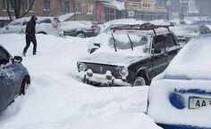 Carros presos na neve durante tempestade de neve na em Kiev; o Ministério de Situações de Emergência e o exército foram enviados para resgatar as pessoas com carros enterrados na neve durante nevascas na capital ucraniana. Mais de 1.000 veículos presos foram libertados da neve durante as últimas 24 horas em Kiev, segundo o Ministério de Emergência