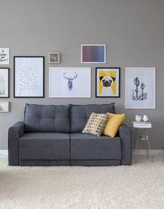 Um sofá retrátil que une conforto e beleza. Os quadros garantem o charme da sala de estar.