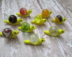 These snails were hand-sculpted from polymer clay. Wire was used to form antennas. Luminous marbles serve as the shells. The sunlight plays