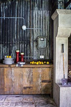 Sector cocina del quincho de una casa con muebles y mesada hechos en madera rústica de lapacho, sobre la que hay platos blancos y limones. Las paredes son de chapa acanalada y el piso de piedra.