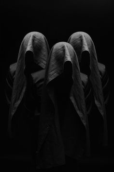 Mysterious black cloaked figures, à la Terry Pratchett's Auditors from the Discworld series.