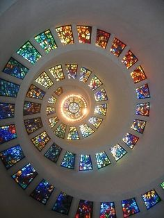 """Stained Glass Spiral Ceiling in a Dallas, TX Chapel.  Chapel of Thanksgiving, a small, spiral tower that features an enclave for prayerful thanks. The entrance to the chapel is at the end of a 125-foot bridge that runs over a cascading waterfall. Inside the chapel, the spiral is topped with stained glass """"Glory Window"""", one of largest horizontally mounted stained-glass pieces in the world."""