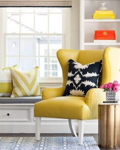 Beautiful living room features a built-in window seat with storage topped with a gray seat cushion, yellow striped pillow and yellow Greek key pillow alongside a modern yellow wingback chair accented with a black and white leaf print pillow situated beside a Arteriors Zeb Corrugated Antique Brass Accent Table.