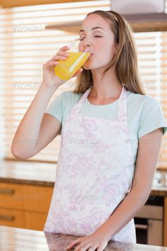 Buy Portrait of a woman drinking orange juice by Wavebreakmedia on PhotoDune. Portrait of a woman drinking orange juice in her kitchen Citrus Juicer, Orange Juice, Drinking, Author, Stock Photos, Woman, Portrait, Search, Beverage
