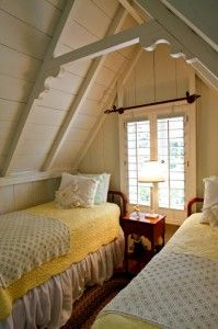 Cozy bedroom under the eaves in one of the famous California Moody Cottages.