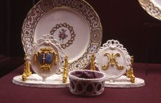 A Sèvres plate from Marie Antoinette's dessert service, with two pastillage table markers, one with her cipher, the other with the arms of the Princesse de Lamballe. The Princesse ordered an identical dessert service from Sèvres.