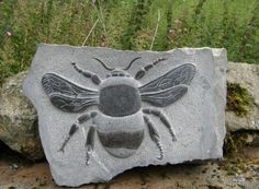 Black weardale marble Wall Mounted or Wall Hanging sculpture by artist Peter Graham titled: '`Bumble Bee` (Carved stone Outsize Big Large Low Relief statuette)'